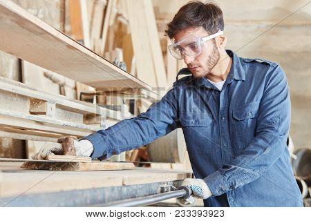 Carpentry apprentice with belt sander grinding wood