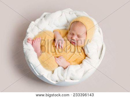 Sleeping newborn baby curled up on round basket