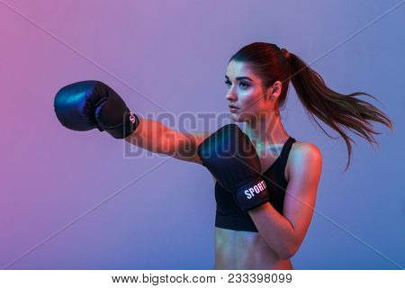 Feminine woman fighter 20s in sportswear and black boxing gloves throwing punches while training isolated over dark background