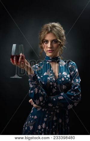 Attractive woman wearing blue fashionable dress with stylish flower print is holding glass full of red wine. Model having pretty hairstyle with curles and day make up. Frontview on dark background. poster