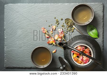 Green Tea With Rose Flower On Black Slate Background. Top View With Copy Space.