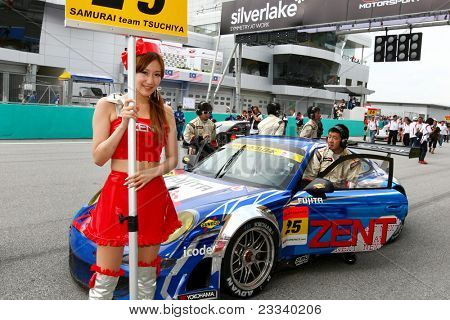 SEPANG, MALAYSIA - JUNE 19: Samurai Team Tsuchiya's race queen poses in front of the team's car at the Sepang Circuit at the start of the Japan SUPER GT Round 3 race on June 19, 2011 in Sepang, Malaysia.