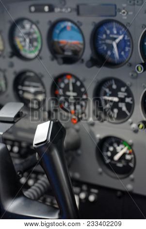Plane cockpit instruments and indicators. Only steering wheel is in focus, other instruments blured by lens.