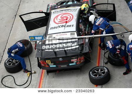 SEPANG - JUNE 19: apr team's pit crew prepares to refuel and change tires during a pit-stop of the Japan SUPER GT Round 3 race on June 19, 2011 in Sepang International Circuit, Malaysia.