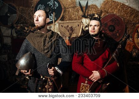 Serious militant Vikings stand with a weapon in hands. Portrait of two warriors in ancient clothes with a gun against the backdrop of skins and flags of the Vikings. poster