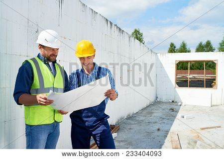 Portrait Of Two Construction Workers Wearing Hardhats And Reflective Vests  Discussing Floor Plans O