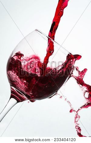 Close Up Of The Pouring With Spill Of Red Wine On A Glass Against A White Background