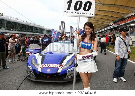 SEPANG, MALAYSIA - JUNE 19: Team Kunimitsu's race queen poses in front of the team car at the Sepang International Circuit before the Japan SUPER GT Round 3 race on June 19, 2011 in Sepang, Malaysia.