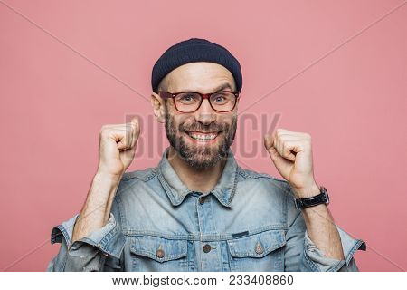 Happy Bearded Male With Blue Eyes And Cheerful Expression Clenches Fists, Feels To Be Winner, Demons