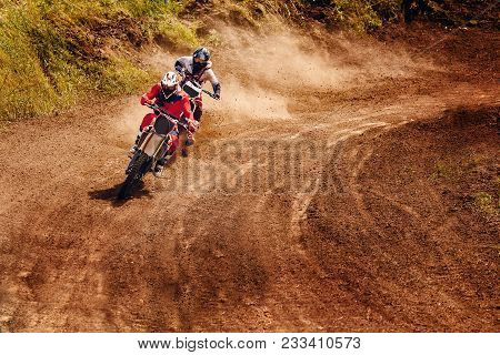 Racer On Dirtbike Motorcycle Jumps And Takes Off Over Track, In Background Opponent Is Catching Up.