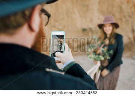 Handsome Groom Taking Photo Of Beautiful Bride On His Phone Stock Image. Artwork. Selective Focus On