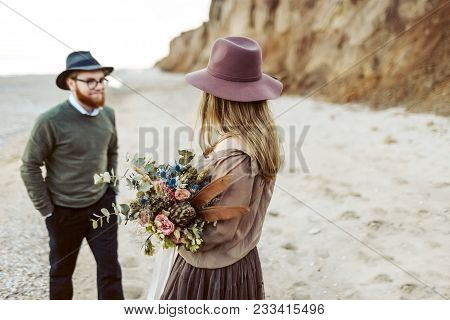 Country Style Wedding. Newlyweds With Rustic Bouquet In Hands Stand On Seashore. Outdoors. Selective