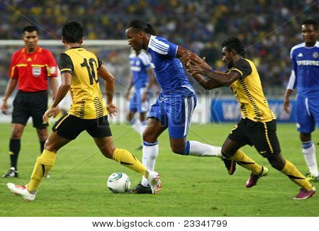 BUKIT JALIL, MALAYSIA - JULY 21: Chelsea's Didier Drogba (blue) dribbles the ball past Malaysian players at the National Stadium on July 21, 2011 in Bukit Jalil, Malaysia. Chelsea won 1-0.