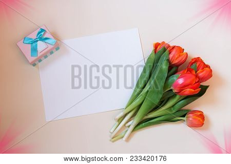 Tulips, Card And Gift Box On Beige Background. Top View With Copy Space.