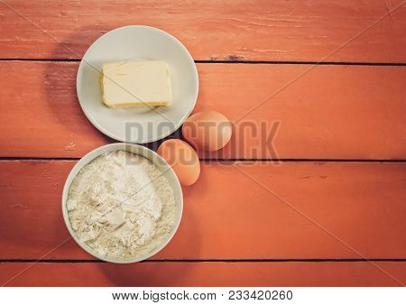 Flour, Eggs And Butter On Rustic Painted Wooden Background. Top View With Copy Space.