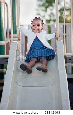 3-year old African American Girl Playing on slide in the Playground