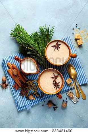 Masala tea chai latte traditional hot Indian teatime ceremony sweet milk with spices, herbs organic infusion healthy beverage in porcelain cup on blue table background poster
