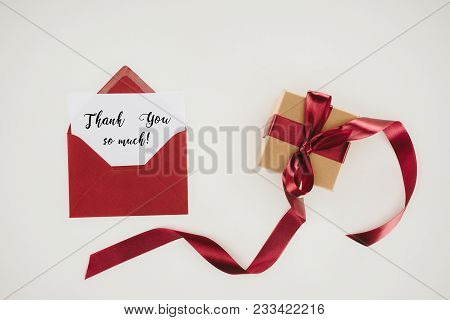 Top View Of Red Envelope With Thank You So Much Lettering On Paper And Gift Box Isolated On White