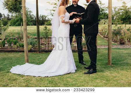 Couple Standing Before The Priest For Wedding Ceremony Outdoors In The Park. Bride And Groom Standin