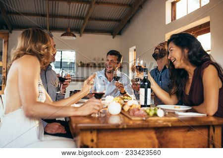 Group Of Friends Gathered Around A Table In Kitchen To Share A Meal And Have A Good Time Together. M