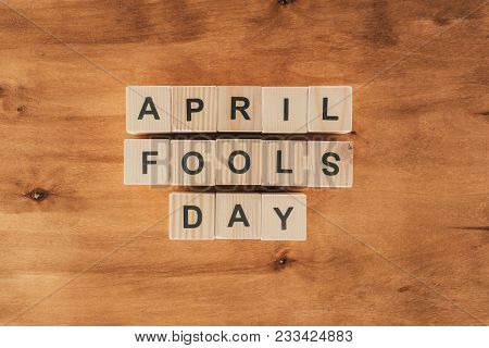 top view of arranged wooden cubes in april fools day lettering on wooden tabletop, 1 april holiday concept poster