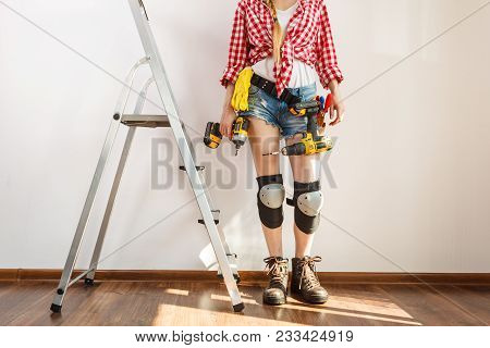 Woman Fully Equipped With Work Repairing Tools About To Stand On Ladder. Female Repairs Indoor.
