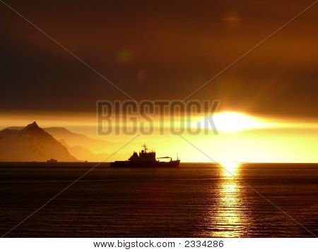 Sunset In Antarctica With Boat Profile