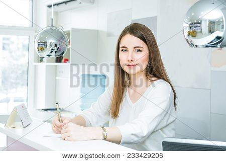 Portrait Of Friendly Young Woman Looking At Camera, Writing Note Behind The Reception Desk. Administ