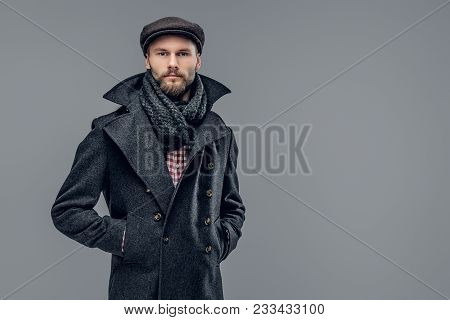 Portrait Of A Bearded Hipster Man Dressed In A Gray Jacket And A Wool Cap Isolated On Grey Backgroun