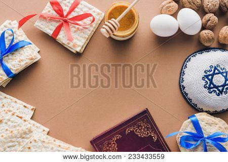 Top View Of Traditional Book With Text In Hebrew, Kippah And Matza On Brown Table