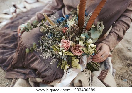Bride In Brown Clothes With A Rustic Bouquet Sit On The Sand. Artwork. Country Style Wedding. Select