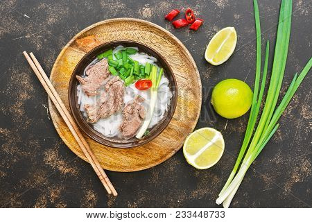 Vietnamese Soup Pho Dish. Asian Cuisine. Vietnamese Soup On A Dark Rustic Background. View From Abov