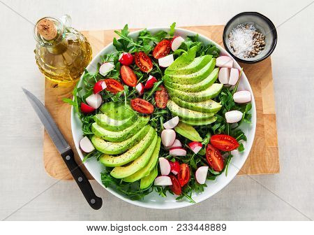Healthy Fresh Vegetarian Salad From Avocado, Cherry Tomato, Radishes And Rucola With Olive Oil And S