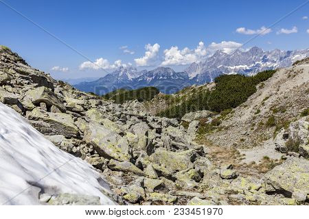 View From Mountain Rippetegg With Some Snow And Rocks To Distant Mountain Dachstein In Austria