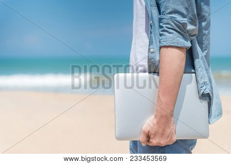Male Hand Holding Laptop On The Beach, Working Outdoor In Summer Season, Digital Nomad Man Lifestyle