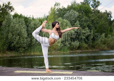 Young, Beautiful Girl Performs Yoga Asanas On The Lake Shore. Nature, Zen, Lifestyle