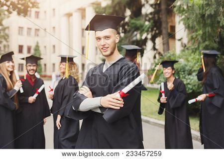 Young Smiling Male On His Graduation Day In University Standing With Multiethnic Group Of People. Ed