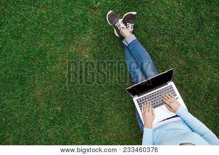 Top View Of Girl Sitting In Park On The Green Grass With Laptop, Hands On Keyboard. Copy Space On Co