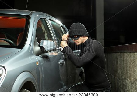 A thief with a robbery mask trying to steal an autobmobile