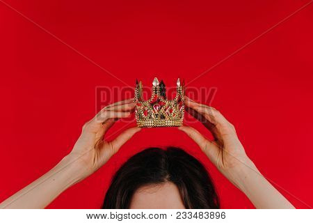 Gold Crown On A Red Background In Female Hands Over Her Head, The Girl Holds A Toy Crown Over Her He