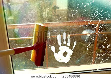 Hand Print On Dirty Window And Squeegee Cleaning The Glass. Cleaning Windows With A Squeegee.