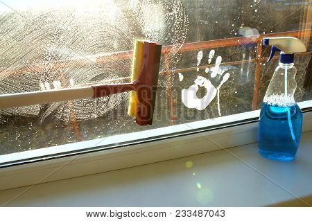 Hand Print On Dirty Window And Squeegee Cleaning The Glass. Glass Squeegee And Bottle Of Window Clea