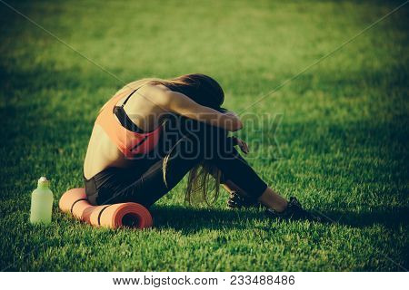 Health, bodycare, wellness. Tired woman in sportswear relax after workout, training. Sportswoman sit on green grass with gym equipment on summer. Backache, back pain, fatigue. Sport, training, workout poster