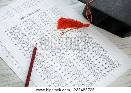 Answer sheets with pencil and graduation cap on table. Passing of exams