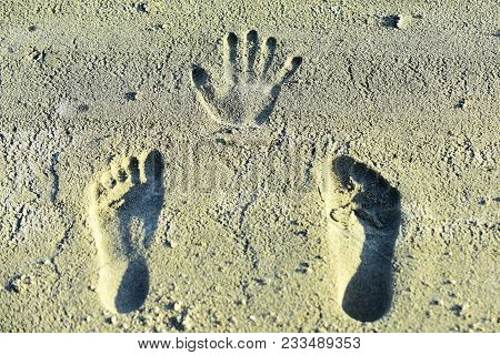 Handprint And Footprints On Sand. Human Imprints, Prints, Tracks On Sandy Surface. Palm, Fingers, Fe