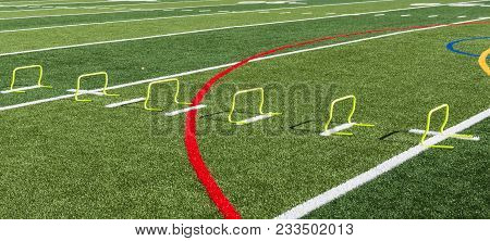 Twelve Inch Yellow Mini Banana Step Hurdles Are Lined Up On A Green Turf Field For Track And Field S