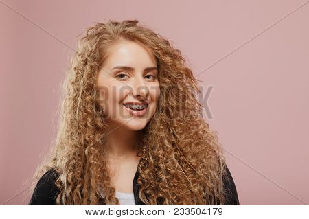 Girl Braces. Young Girl With Braces For Teeth On Pink Background, Curly Hair, Modern Clothes. Concep