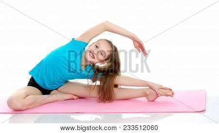 Girl Gymnast Performs An Acrobatic Element On The Floor.the Concept Of Childhood, Sport, A Healthy L