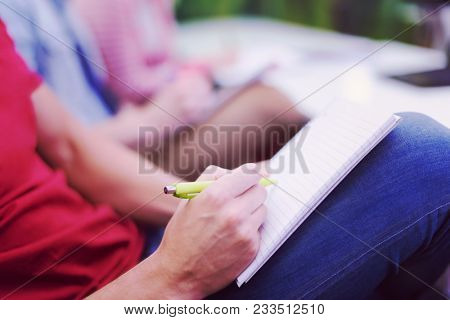 male student taking notes in classroom. business education concept, casual young businessman on seminar training