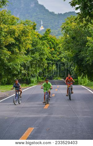 Lopburi, Thailand - July 21, 2013: Three Boys With Different Color Shirts Riding Bicycles On Rural R